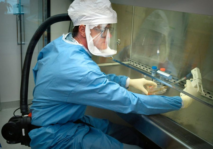 """""""This photograph depicts one of the Centers for Disease Control's (CDC) staff microbiologists using an electronic pipette to extract reconstructed 1918 Pandemic Influenza virus from a vial containing a supernatant culture medium."""""""